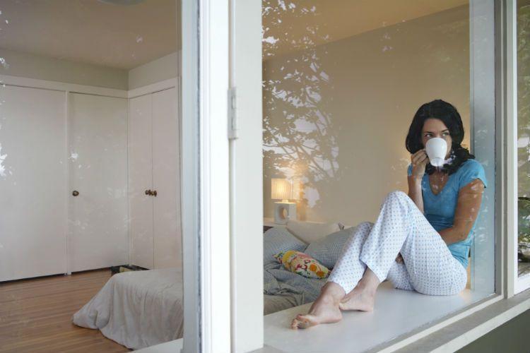 Chica desayunando frente a ventana PVC